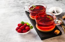 hot raspberry tea in two transparent cups on a stone table. Fresh berries, cubes of cane sugar and a bag of tea